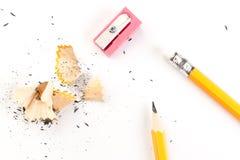 Hölzerner Bleistift lokalisiert auf einem weißen Hintergrund mit Schnitzeln und Bleistiftspitzer stockfotografie