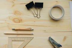 Hölzerner Bleistift, Stift, Dreieck, briefpapier Klipp, hefter auf dem Schreibtisch im Tageslicht Bürotisch Lizenzfreie Stockfotos