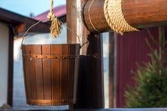 Hölzerner Brunnen. Eimer auf einem Seil Stockfotos