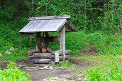 Hölzerner Brunnen im Wald Stockbild