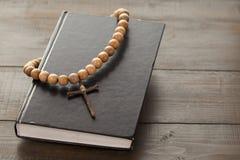 Hölzerner Christian Cross auf der geschlossenen Bibel Stockbilder