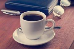 Hölzerner Desktop mit Kaffeetasse, Tagebuch, Stift und Brillen, Weinlese gefiltert, keine Leute, gerichtet auf Kaffee Lizenzfreie Stockfotografie