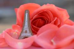 Hölzerner Eiffel und Rotrose auf Blumenblättern Stockfotografie