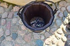 Hölzerner Eimer der großen Runde mit Münzen lizenzfreie stockfotografie