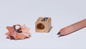 hölzerner einfacher Bleistift, ein Bleistiftspitzer und Schnitzel Lizenzfreie Stockfotografie
