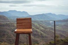 Hölzerner einzelner Stuhl auf dem Balkon mit Ansicht des ruhigen mountai lizenzfreie stockbilder