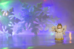 Hölzerner Engel auf blauem Schneeflockenhintergrund Lizenzfreies Stockbild