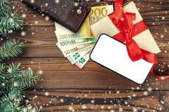 Hölzerner Feiertagshintergrund, Geschenk für geliebte Raum für Text am Telefon Beschneidungspfad eingeschlossen Effekt von Schnee stockbild
