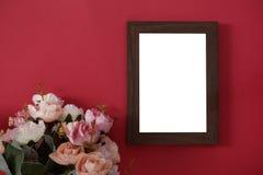 Hölzerner Fotorahmen des Modells mit Raum für Text oder Bild auf rotem Hintergrund und Blume stockbild
