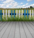 Hölzerner Fußboden mit Zaun und grünem Gras Lizenzfreie Stockbilder