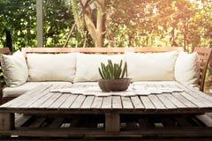 Hölzerner Gartenklubsessel mit Kissen und kleiner Kaktus auf Stockfoto