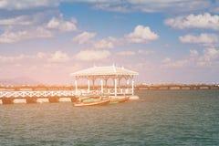 Hölzerner Gehweg über Seeküstenbehälterboot lizenzfreie stockfotos