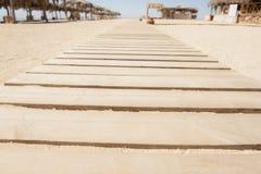 Hölzerner Gehweg auf einem Strand Lizenzfreies Stockfoto