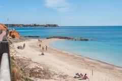 Hölzerner Gehweg auf einer Klippe über einem sandigen Strand an einem klaren Sommertag in Spanien lizenzfreie stockfotos
