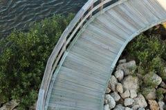 Hölzerner Gehweg entlang Wasser Stockfotografie