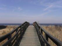 Hölzerner Gehweg zum auf den Strand zu setzen stockbild
