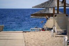 Hölzerner Gehweg, zum des Strandes mit Sonnenschutz zu versanden Stockfotos
