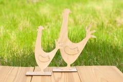 Hölzerner Hahn und Huhn auf grünem Frühlingshintergrund Stockbilder