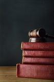 Hölzerner Hammer, der altes Buch-Stapel auf Eichen-Schreibtisch mit Tafel übersteigt Lizenzfreies Stockbild