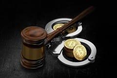 Hölzerner Hammer und Bitcoin-Stapel in den Handschellen stockfoto