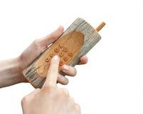 Hölzerner Handy in den Händen trennte Stockbild