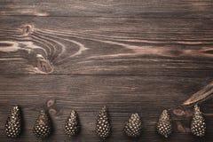 Hölzerner Hintergrund Browns mit ausgeprägter Beschaffenheit Mit goldenen Kegeln an der Unterseite des Bildes Stockbild