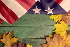 Hölzerner Hintergrund der grünen Weinlese umfasst mit amerikanischer Flagge und Herbstlaub, Kopienraum stockfotos