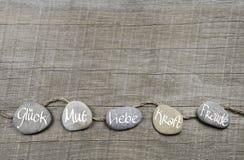 Hölzerner Hintergrund der guten Wünsche mit Steinen und deutscher Text für lu stockbilder