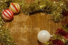 Hölzerner Hintergrund der Weinlese mit Weihnachtsbällen und -lametta Lizenzfreie Stockbilder
