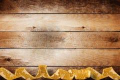 Hölzerner Hintergrund der Weinlese mit wirbelnder Goldborte Lizenzfreie Stockfotos