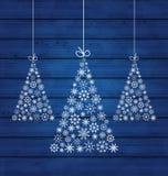 Hölzerner Hintergrund des Feiertags mit den Weihnachtskiefern gemacht von der Schneeflocke Lizenzfreies Stockfoto