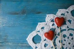 Hölzerner Hintergrund des Türkises im Landhausstil mit zwei roten Herzen auf gewirktem Spitze Doily Stockfotos