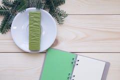 Hölzerner Hintergrund des Weihnachtslichtes mit einem Notizbuch Lizenzfreie Stockfotos