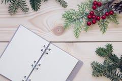 Hölzerner Hintergrund des Weihnachtslichtes mit einem Notizbuch Stockbilder