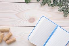 Hölzerner Hintergrund des Weihnachtslichtes mit einem Notizbuch Stockfotografie