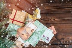 Hölzerner Hintergrund Geschenk und Geld unter Tannenzweigen Raum für Text Beschneidungspfad eingeschlossen Effekt des Lichtes und lizenzfreie stockfotos
