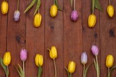 Hölzerner Hintergrund mit den gelben und rosa Tulpen Stockfotografie