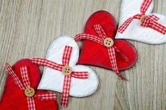 Hölzerner Hintergrund mit den roten und weißen Herzen stockbilder