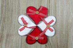 Hölzerner Hintergrund mit den roten und weißen Herzen in Form von Kleeblatt stockbilder