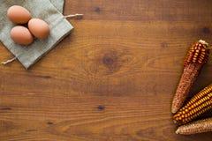Hölzerner Hintergrund mit Eiern, Maiskolben lizenzfreie stockfotografie