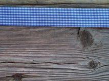 Hölzerner Hintergrund mit einem überprüften Band lizenzfreies stockbild