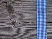 Hölzerner Hintergrund mit einem überprüften Band Stockfotos