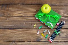 Hölzerner Hintergrund mit einem Buch und Gläser und Bleistifte Grüne APP Stockbilder