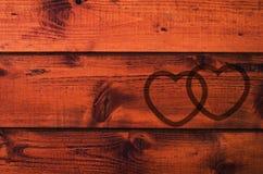 Hölzerner Hintergrund mit Formen von zwei liebevollen Herzen Stockbild