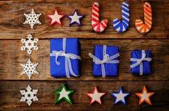 Hölzerner Hintergrund mit hölzernen Spielwaren, Geschenken und den Schneeflocken Lizenzfreies Stockfoto