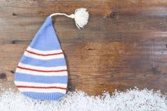 Hölzerner Hintergrund mit Kappe, Schnee auf der Grenze und copyspace Stockfoto