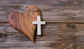 Hölzerner Hintergrund mit olivgrünem Herzen und weißes Kreuz für ein obitua Lizenzfreie Stockbilder