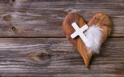Hölzerner Hintergrund mit olivgrünem Herzen und weißes Kreuz für ein obitua Lizenzfreie Stockfotografie