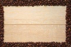 Hölzerner Hintergrund mit Rahmen von Kaffeebohnen stockfotos