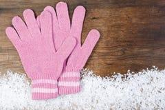 Hölzerner Hintergrund mit rosa Handschuhwinterschnee auf der Grenze Lizenzfreies Stockfoto